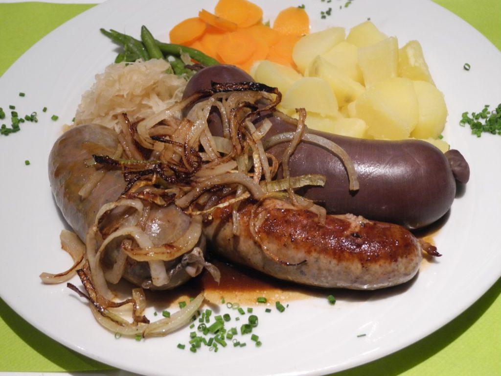 Hausgemachte Blutwurst, Leberwurst und Bratwurst im Teller mit Sauerkraut und Kartoffeln
